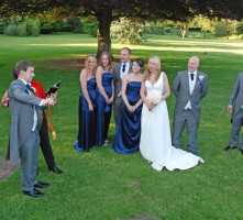 Groom opening champagne with style