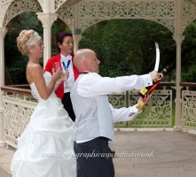 Groom sabrages champagne for his bride at Quex